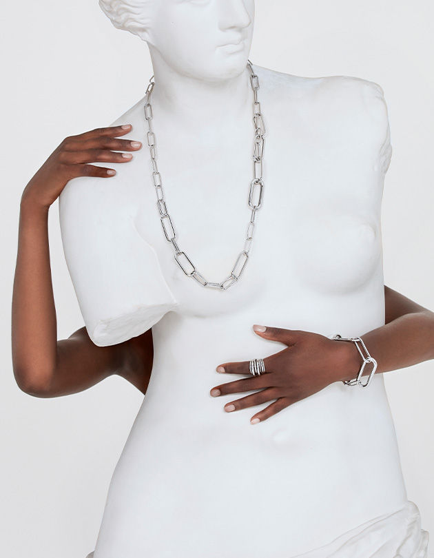 black woman wore bracelet and rings hugs a white statue